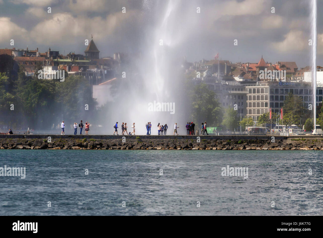 The water jet of Geneva with people in silhouettes on the quay. - Stock Image