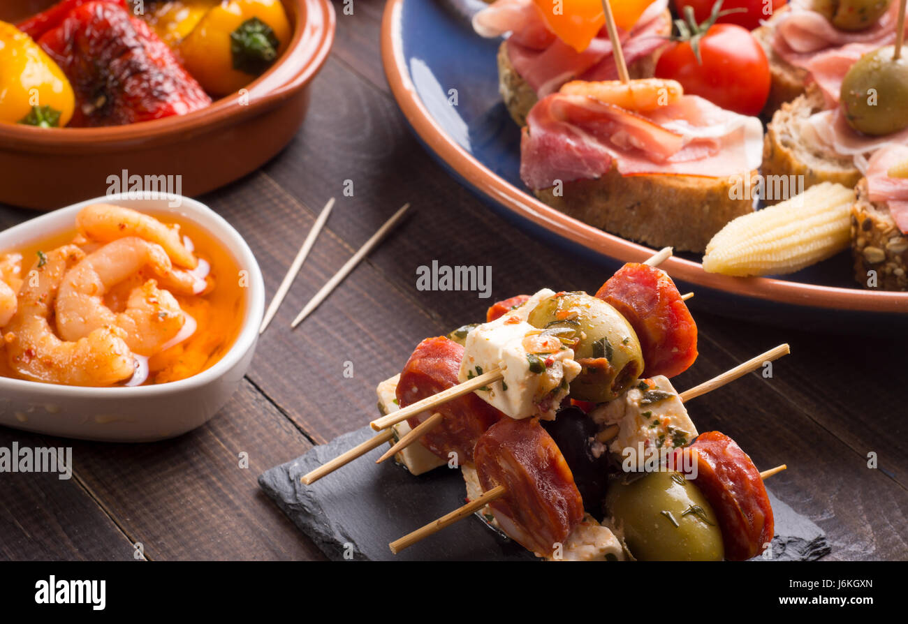 Mixed spanish tapas starters on old wooden table - Stock Image