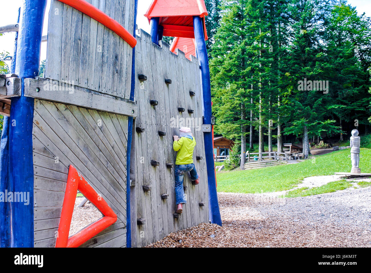 Child climbs the wall. Child in the playground. - Stock Image