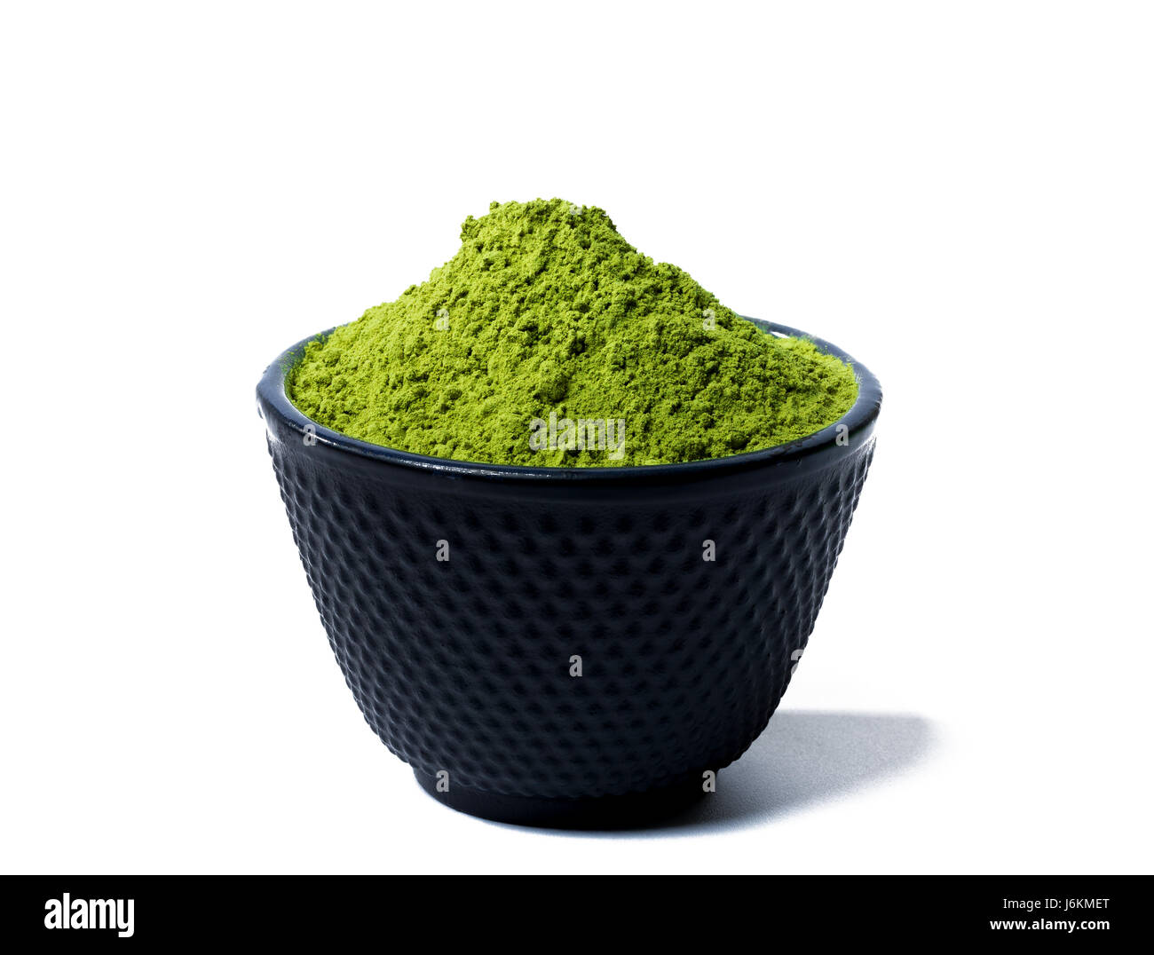 green matcha tea powder in black bowl isolated on white background Stock Photo
