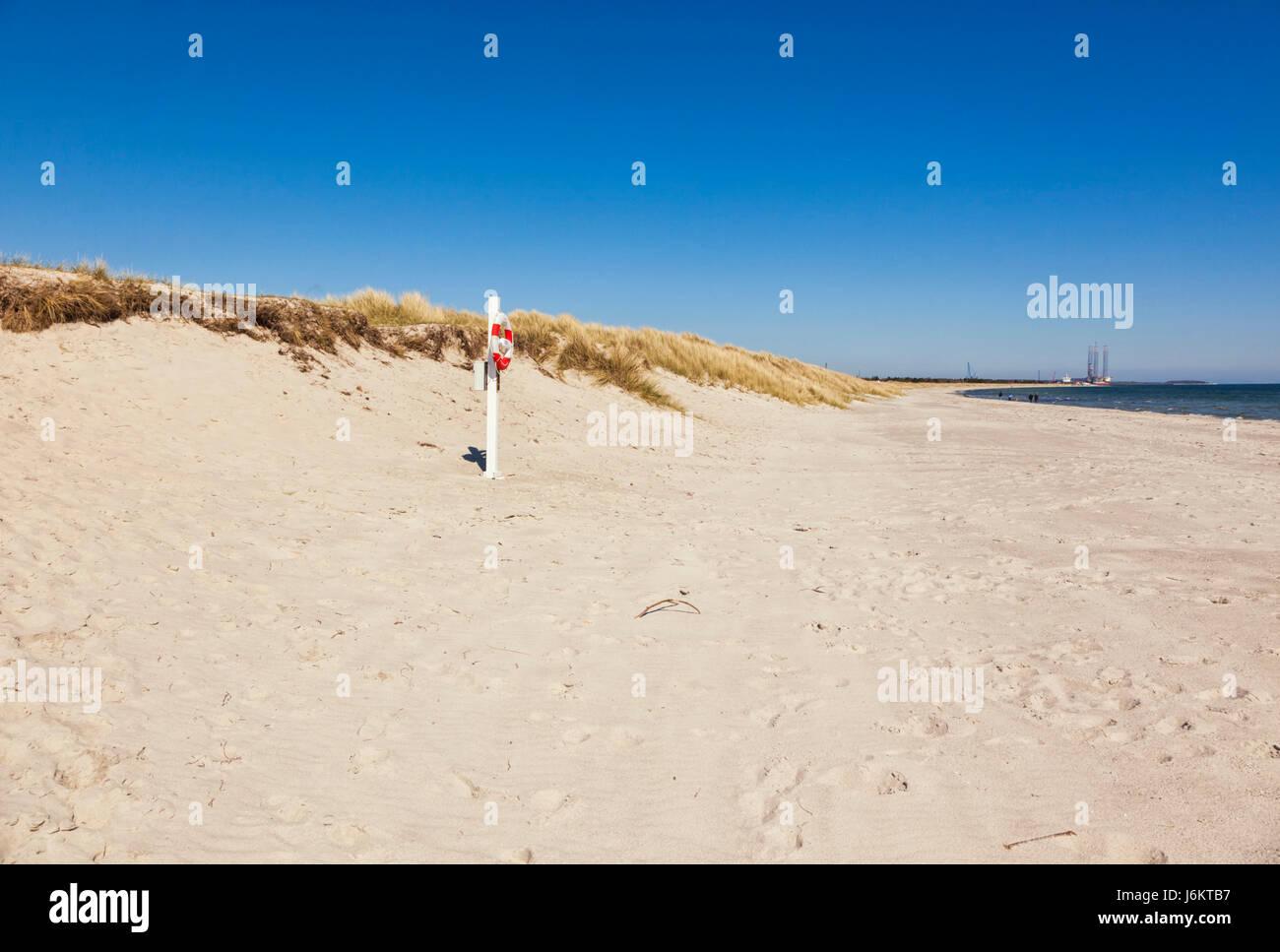 Beach of Grenaa on Baltic Sea coast of Jutland, Denmark. Life buoy in foreground. - Stock Image