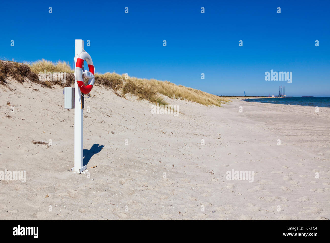 Grenaa, Djursland peninsula, Jutland, Denmark - Life buoy at Grenaa Strand beach. Harbor in background - Stock Image