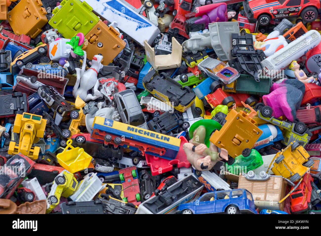 Toy cars and plastic toys in a toy box - Stock Image