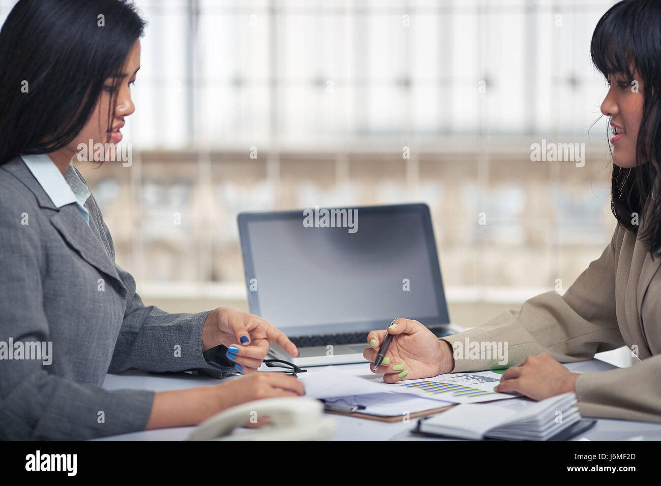 side view of friendly businesswomen discussing and consulting document - Stock Image