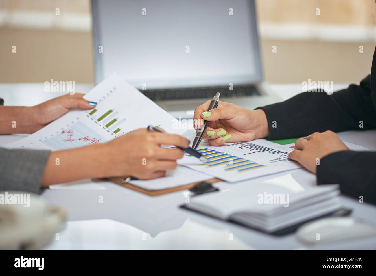 close up image of businesswomen discussing and consulting document - Stock Image