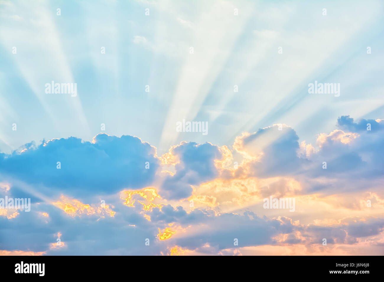 Sunrise sky with sun rays breaking through the clouds - Stock Image