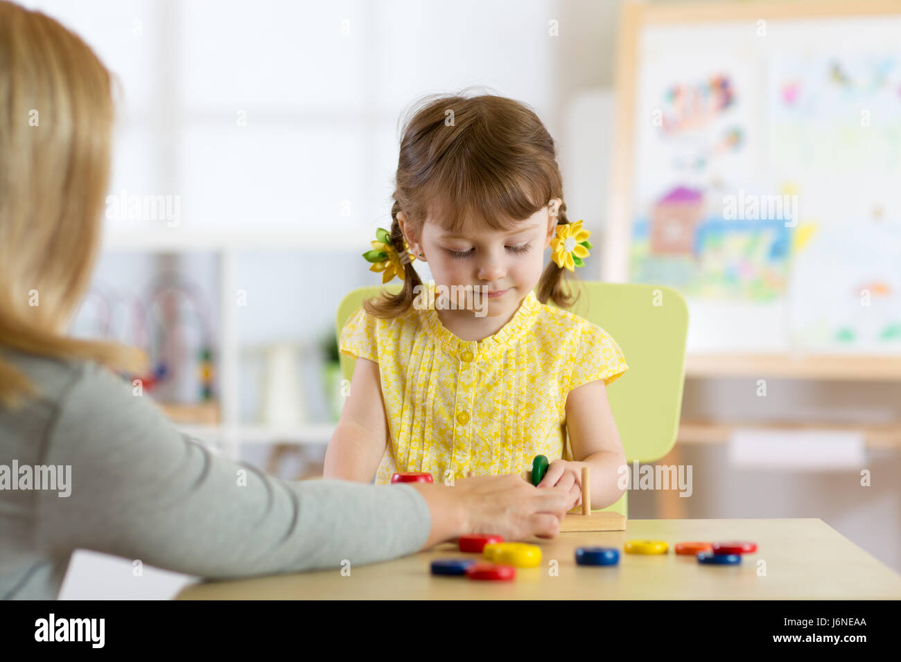 Tutor and preschooler kid playing with educational toys - Stock Image