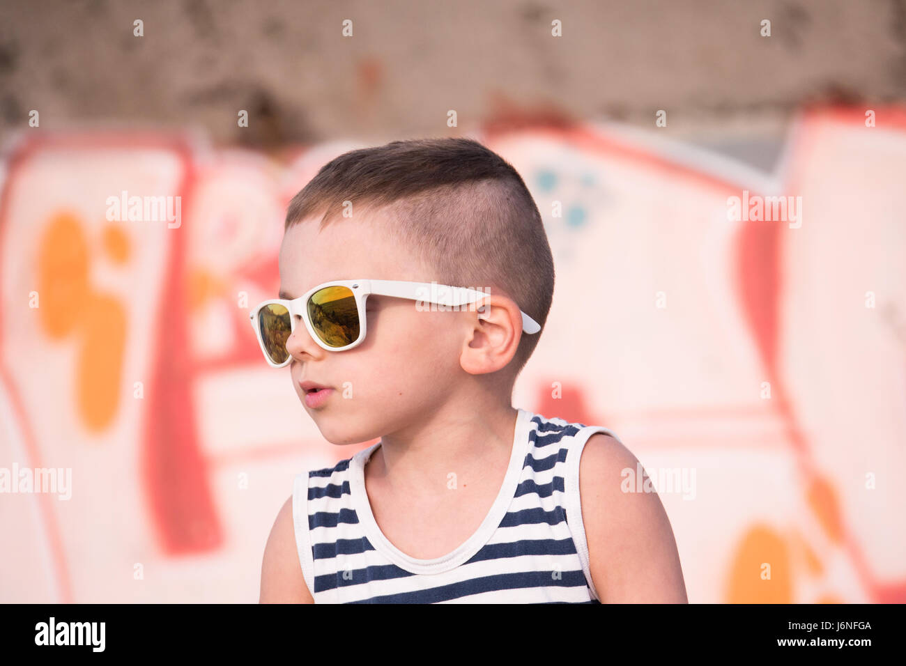 3e1f6ef536a cute little boy wearing trendy white sunglasses and sailor stripes shirt on  graffiti background looking aside