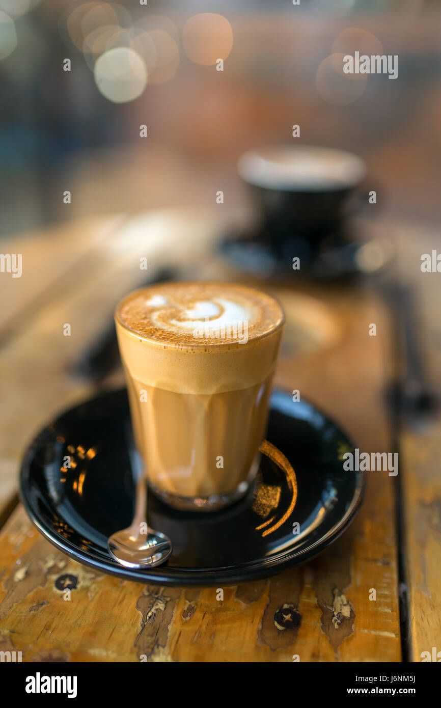Cup of hot piccolo latte coffee on rustic wooden table close-up. Low depth of field - Stock Image