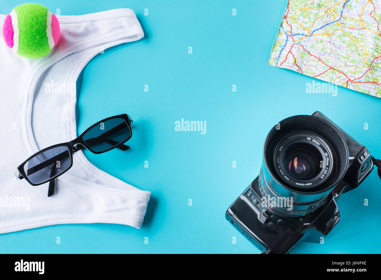 Travel kit: camera, map, t-shirt sun glasses and the small ball. Flat lay composition for social media and travelers. - Stock Image