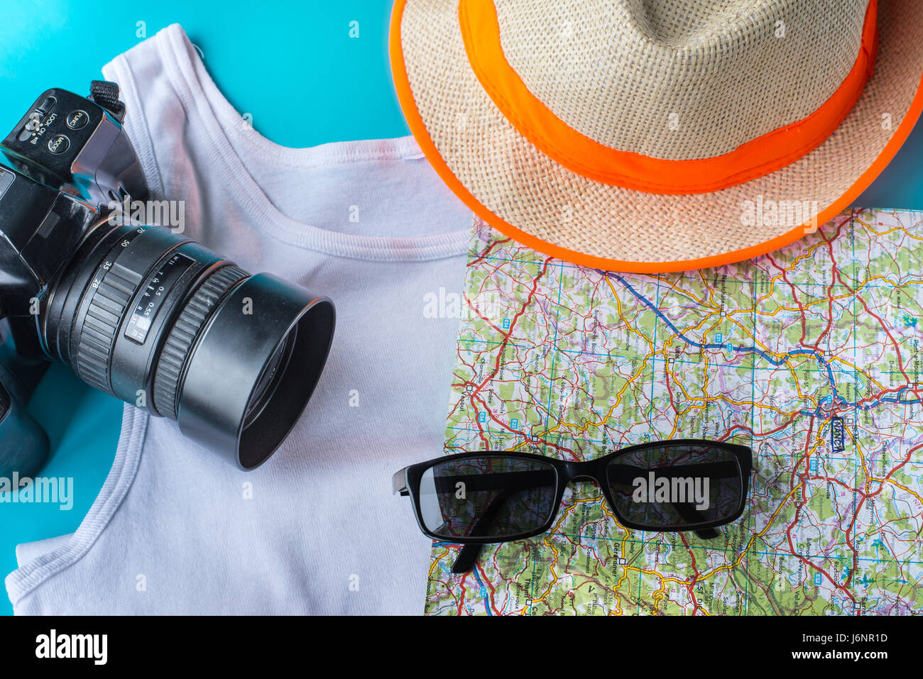 Travel kit: hat, camera, map, t-shirt and sun glasses. Flat lay composition for social media and travelers. overhead - Stock Image