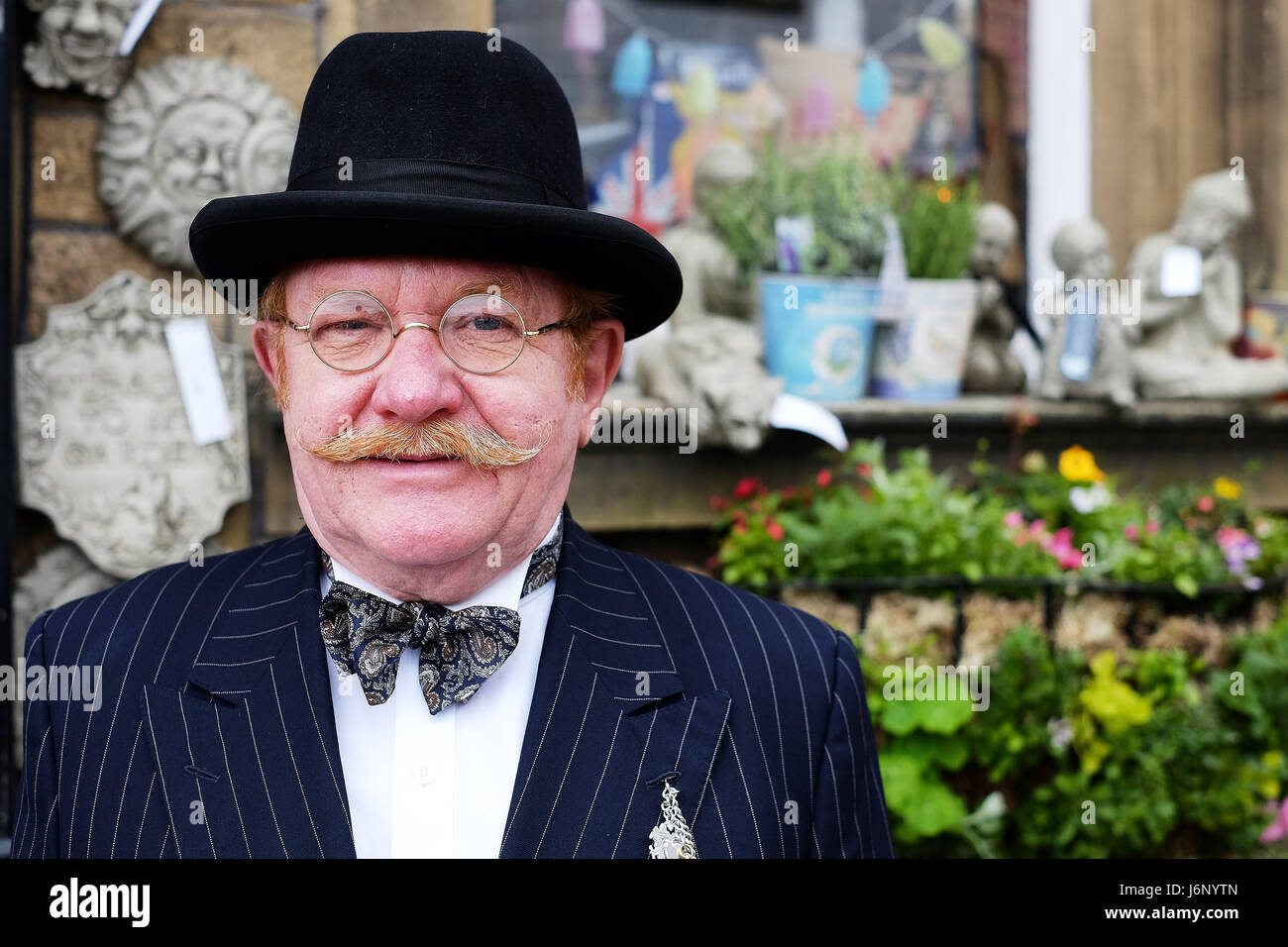 A middle aged man in traditional clothing with a moustache and round glasses - Stock Image