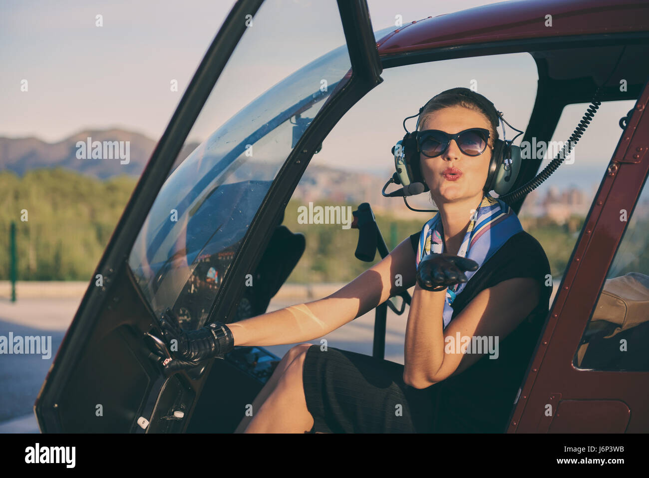 Attractive woman pilot sitting in the helicopter and blowing a kiss - Stock Image