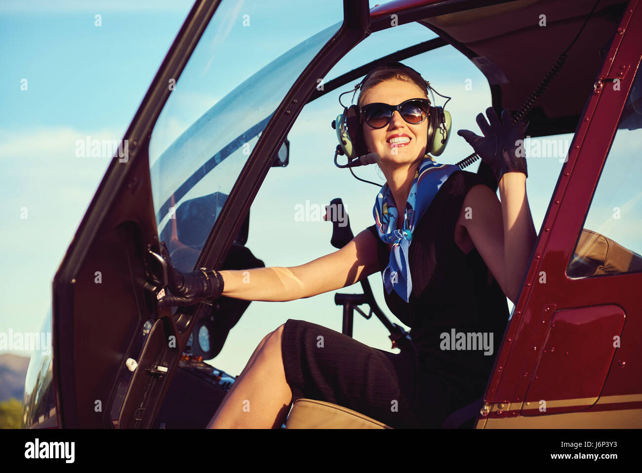 Attractive woman pilot sitting in the helicopter - Stock Image