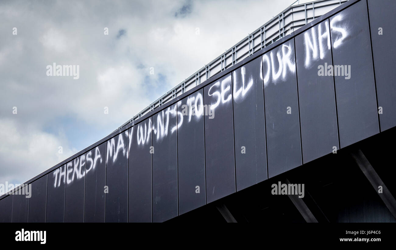 Anti Theresa May and Conservative Party Graffiti over a railway bridge in London. - Stock Image