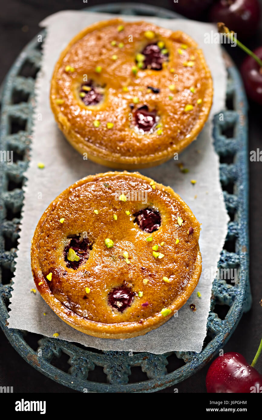 Tarts with cherries and pistachio nuts - Stock Image