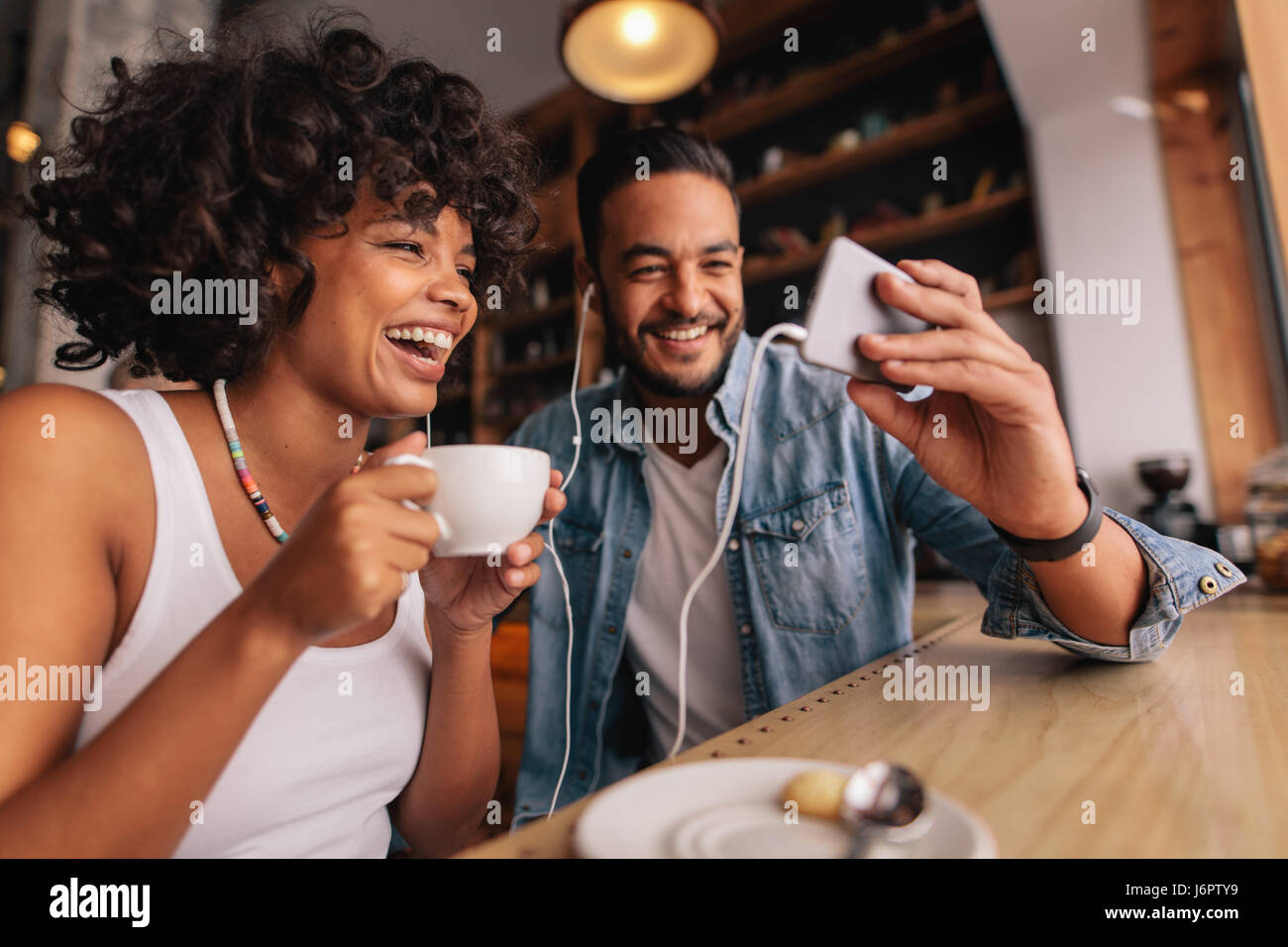 Young man showing something on cellphone to his girlfriend at cafe. Happy young couple sitting at coffee shop having - Stock Image