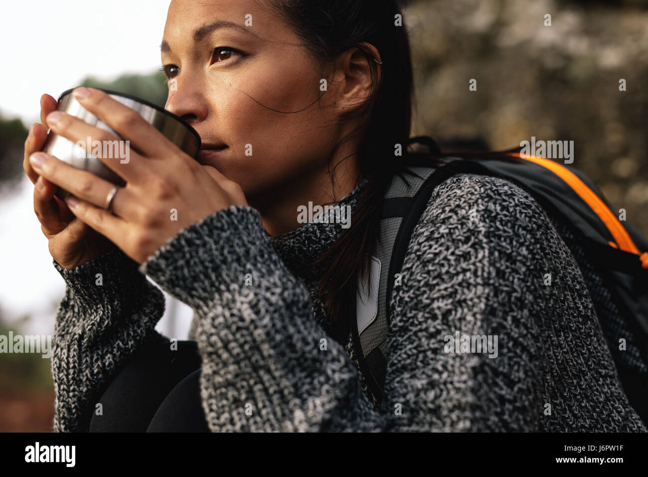 Close up shot of young female hiker drinking coffee. Female hiker taking break during hike. - Stock Image