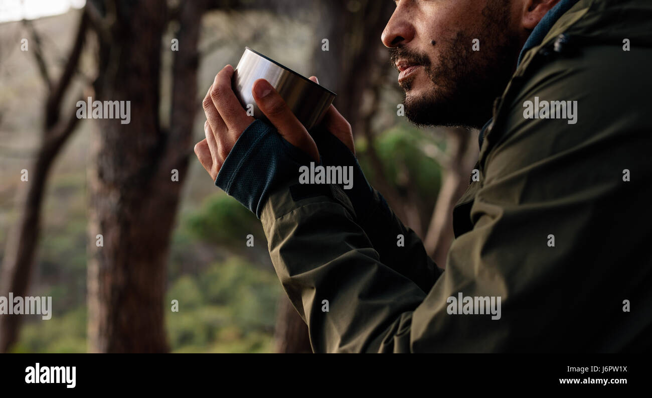 Close up shot of young male hiker drinking coffee. Cropped image of male hiker taking rest during hike. - Stock Image