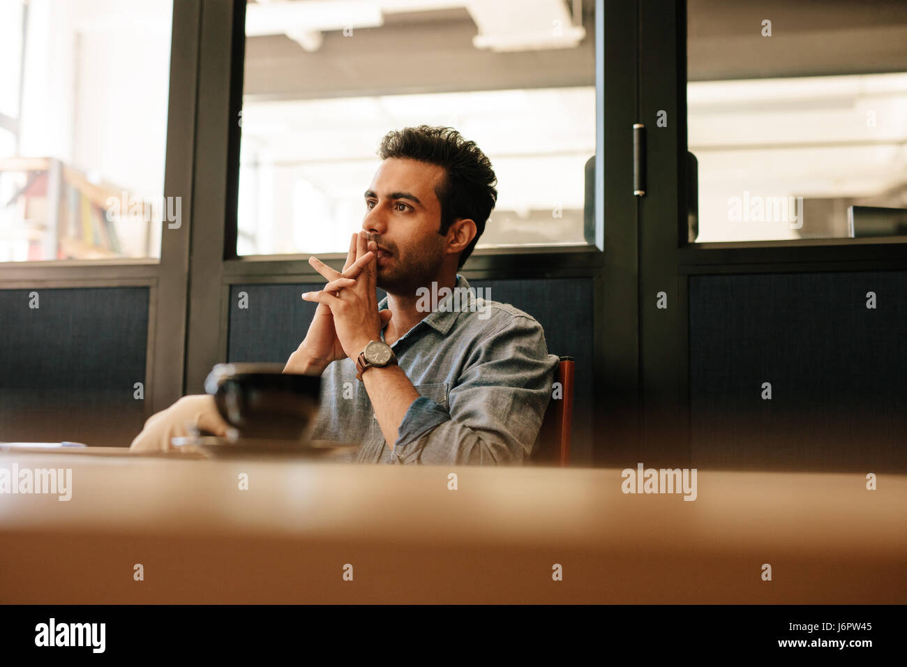 Thoughtful young man sitting at table in conference room and listening to colleague. Man during business meeting. - Stock Image