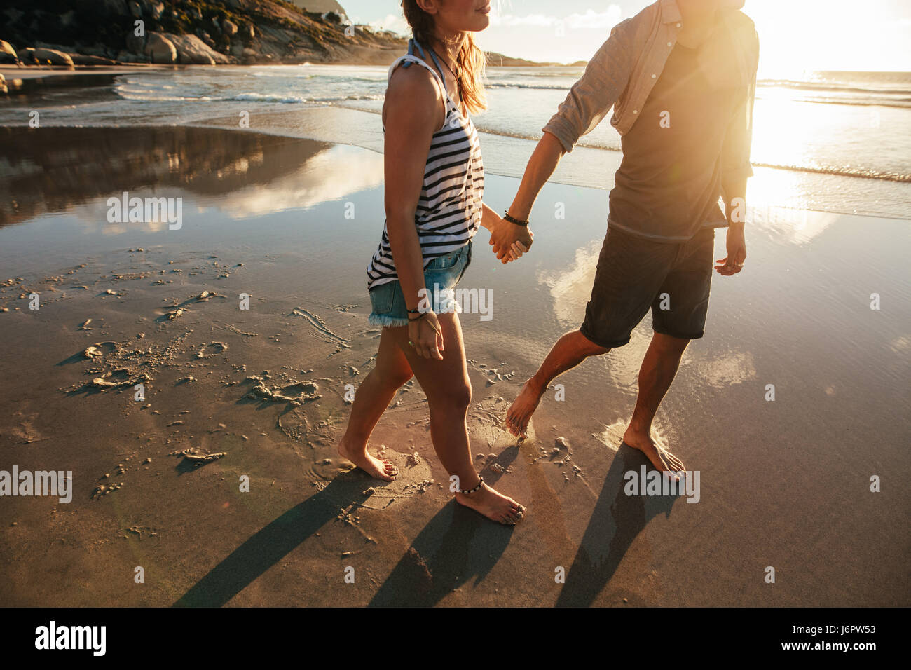 Outdoor shot of loving young couple walking on the sea shore holding hands. Young man and woman walking on the beach - Stock Image