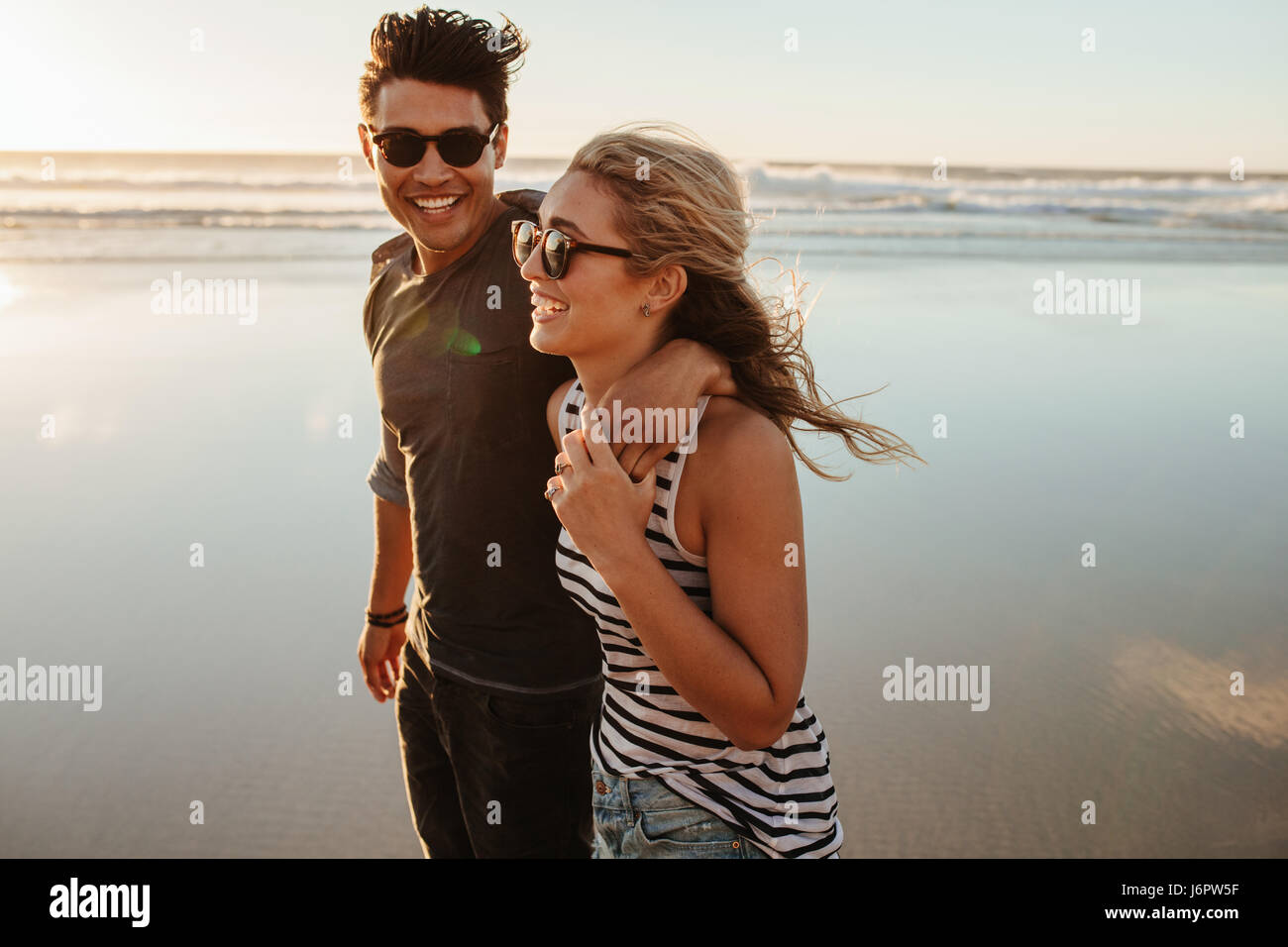 Portrait of romantic young couple walking on sea shore. Man and woman on beach holiday during summertime. - Stock Image