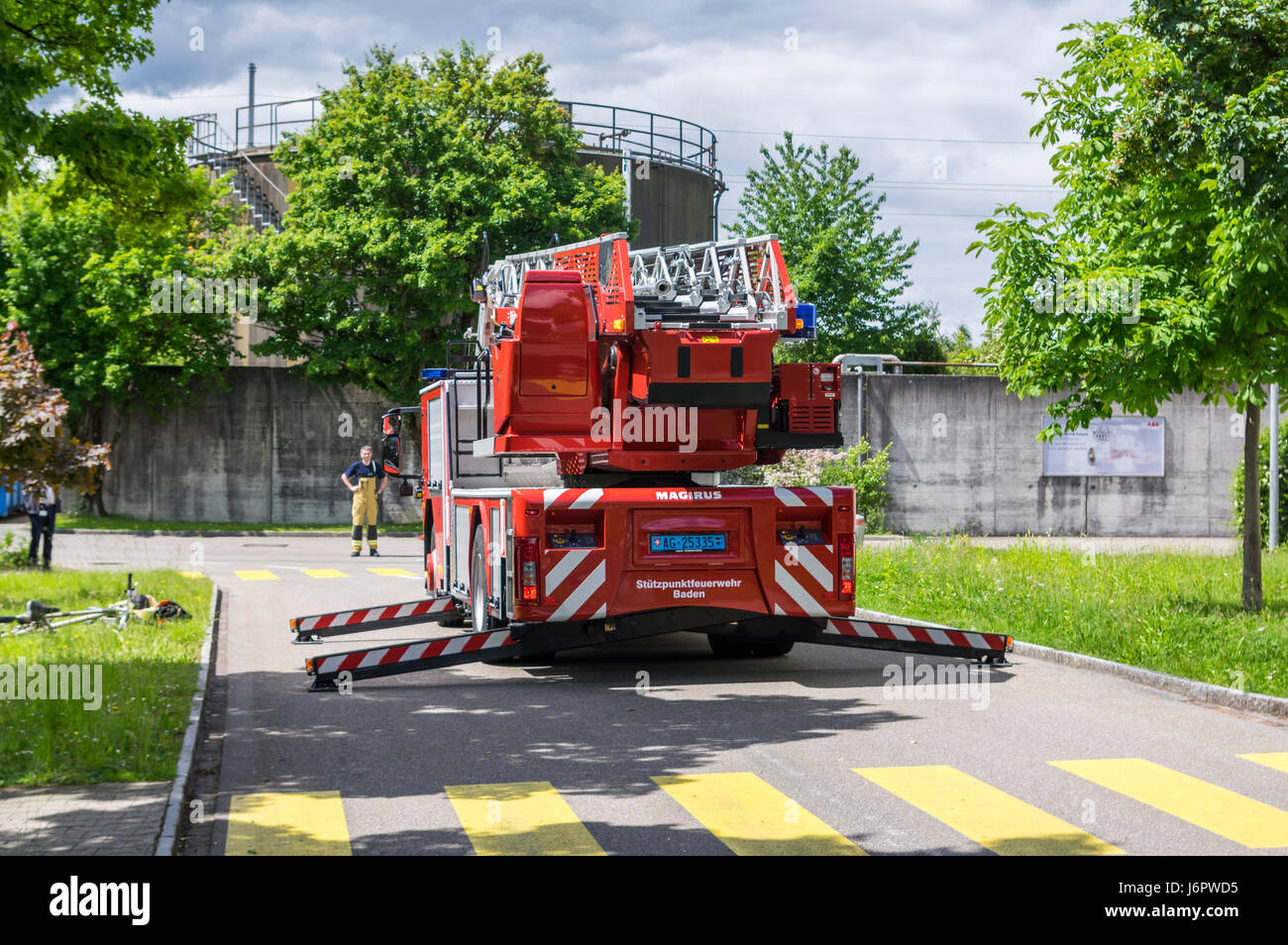 Rear view of an Iveco Magirus 160E30 turntable ladder truck of a Swiss fire brigade. Outriggers/jacks extended, but ladder still retracted. Stock Photo