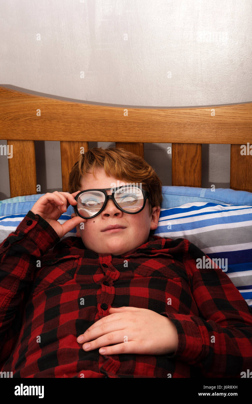 61d3cbb74711 11-year old boy laying on his bed wearing comedy glasses Stock Photo ...