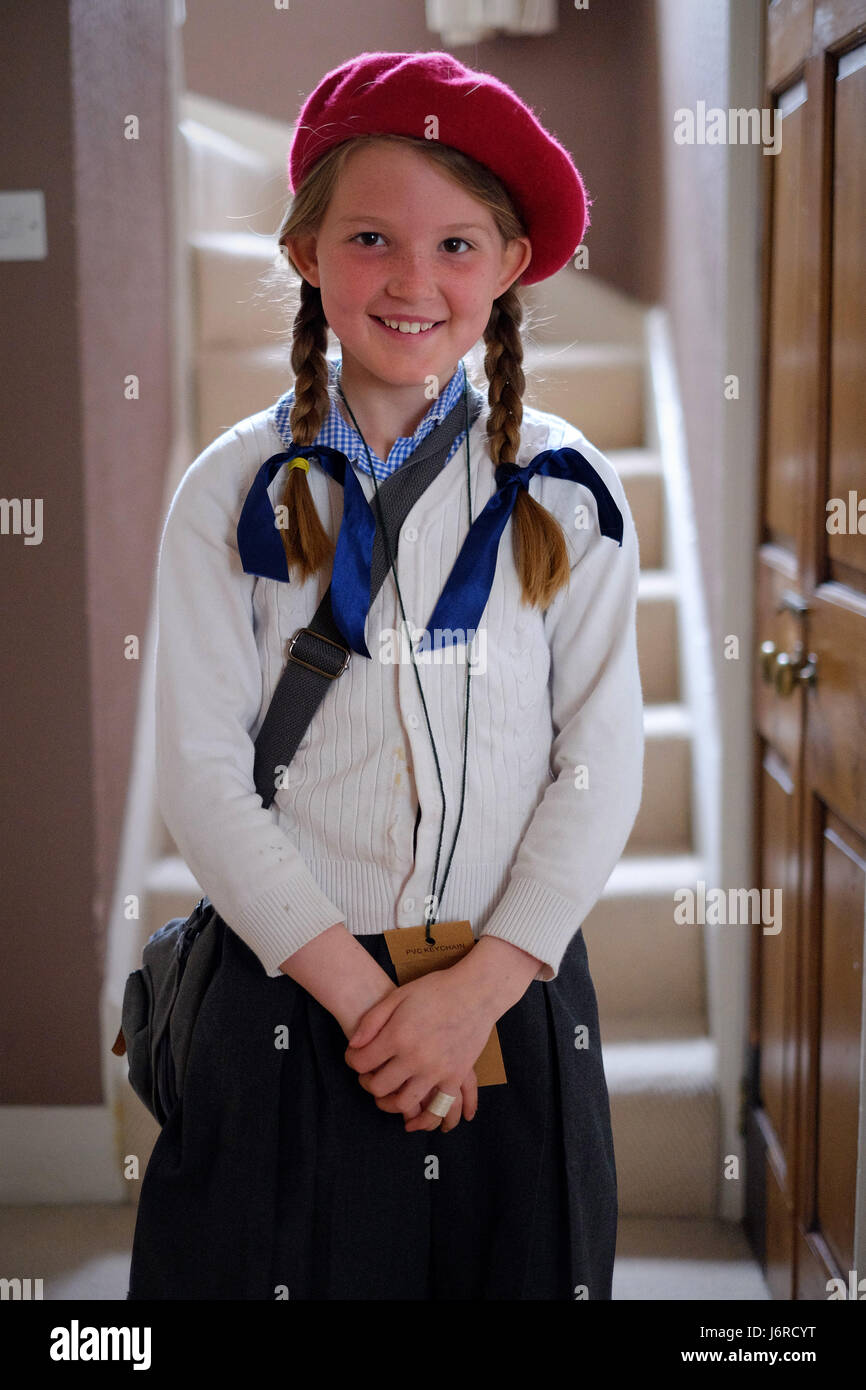 Young girl dresses up as war time evacuee with red beret and school uniform. - Stock Image
