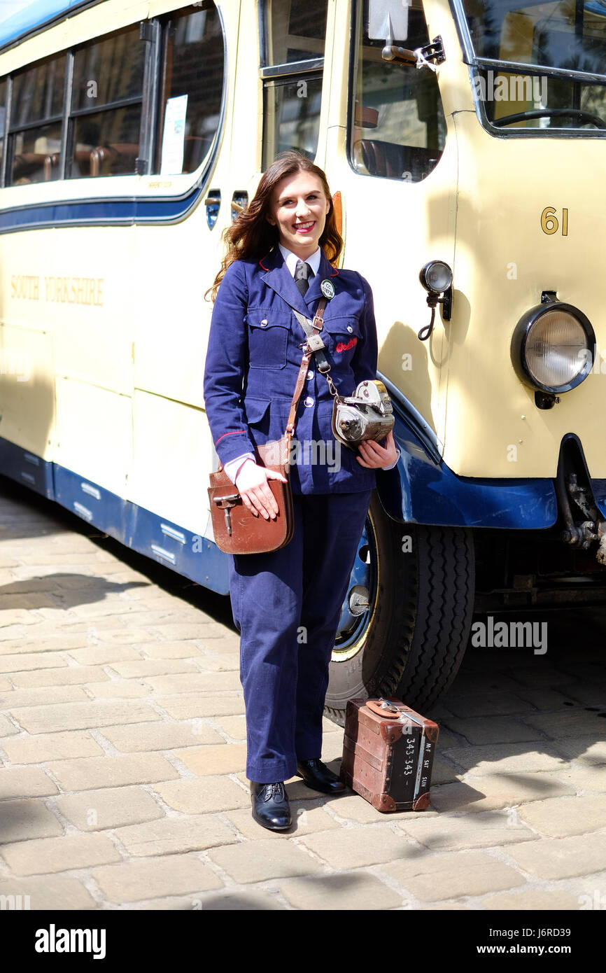 A young woman dresses up as a bus conductor for Haworth's 1940s weekend in Yorkshire. - Stock Image