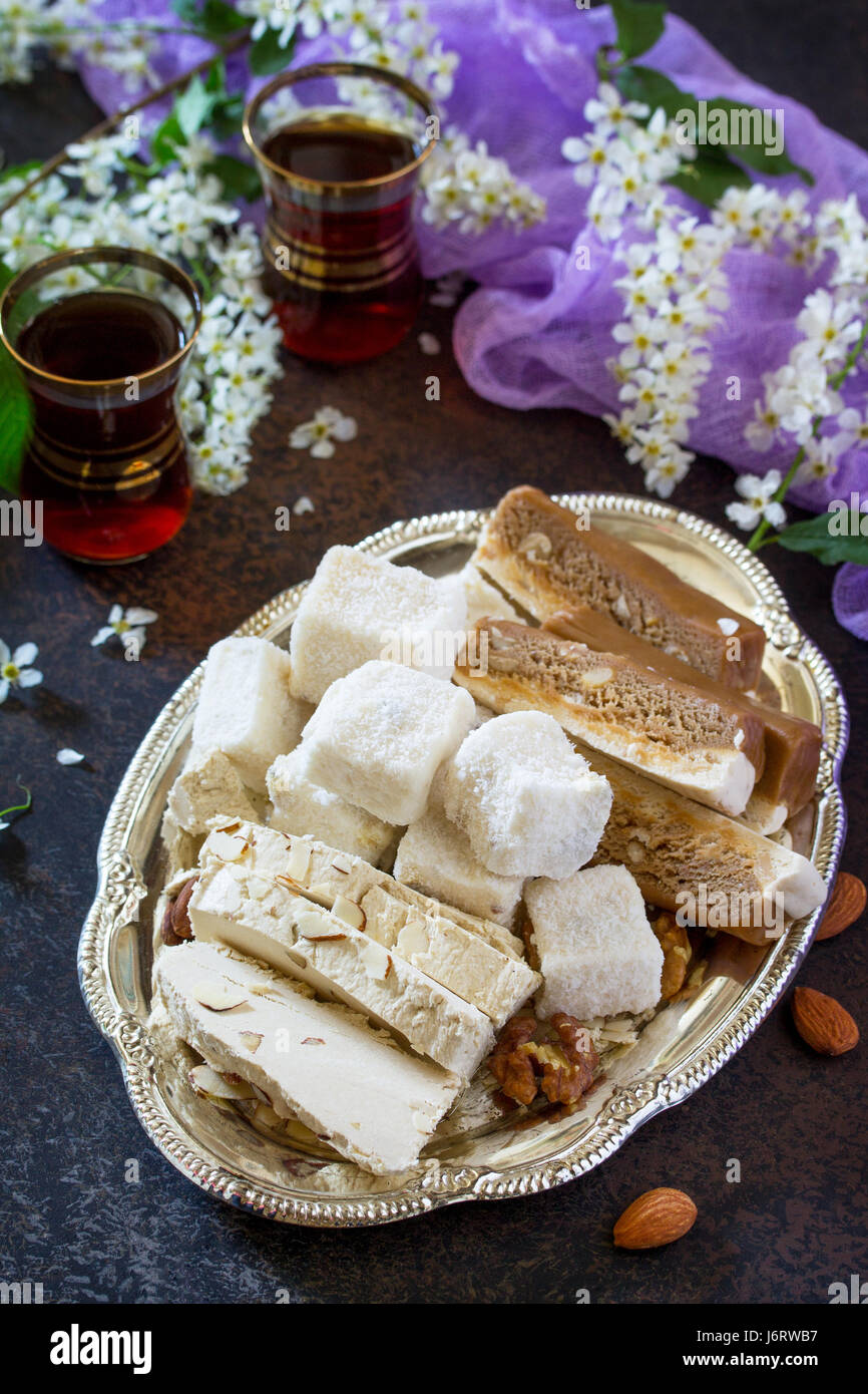 Rahat Lukum, sherbet, halva and tea on the kitchen table. Turkish and Arabic sweets. Ramadan food. - Stock Image