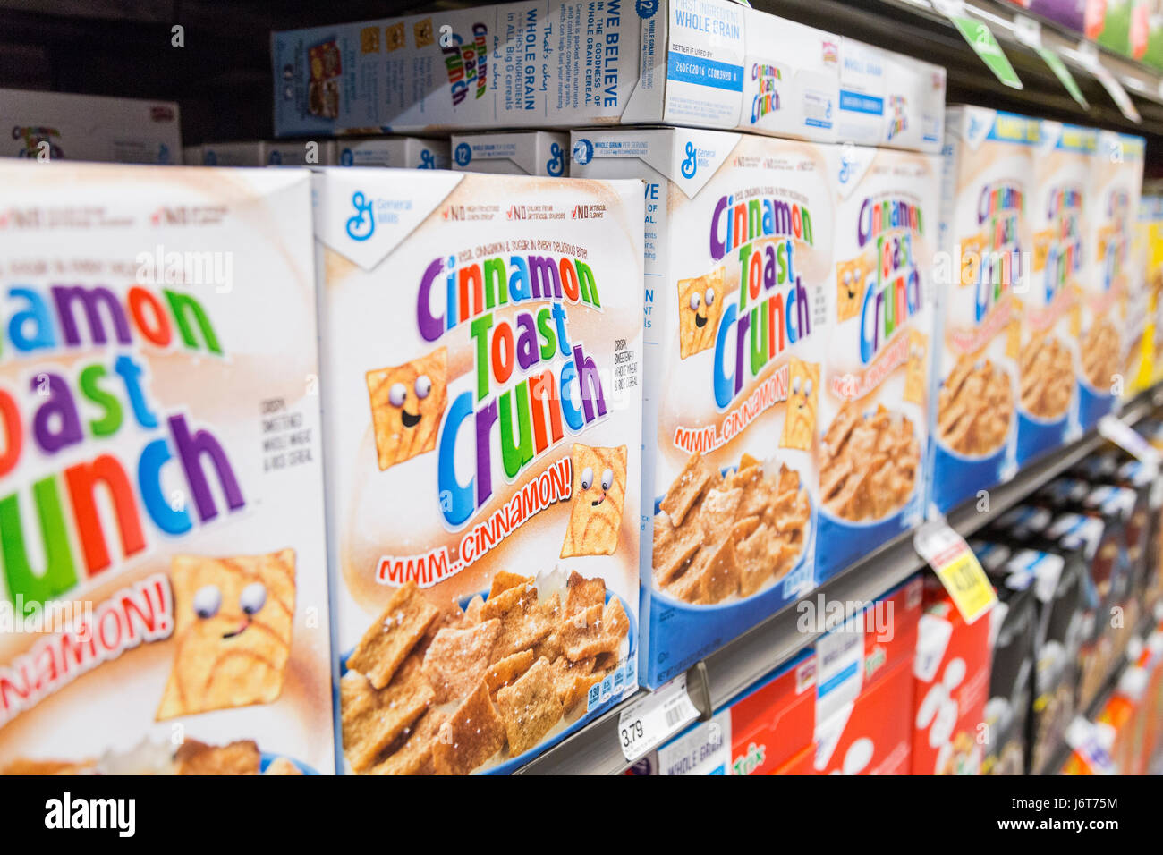boxes of Cinnamon Toast Crunch cereal on shelves at a grocery store - Stock Image