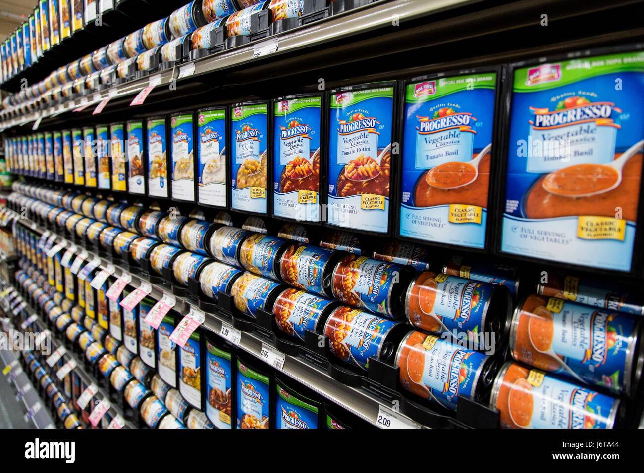 rows of Progresso brand soup cans in a display at a grocery store - Stock Image