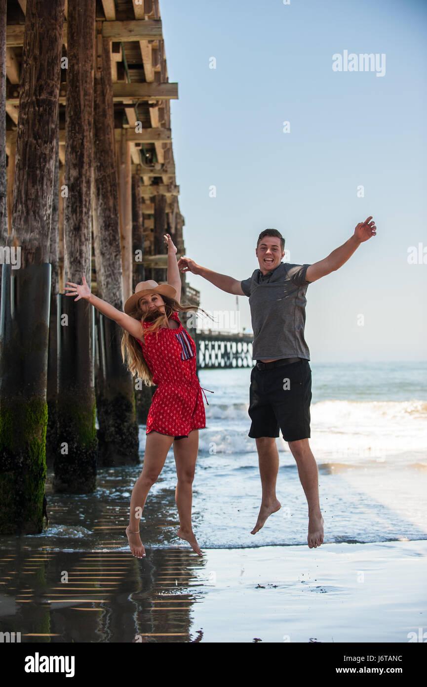 California teen boy and girl jumping for joy next to Ventura Pier. Stock Photo