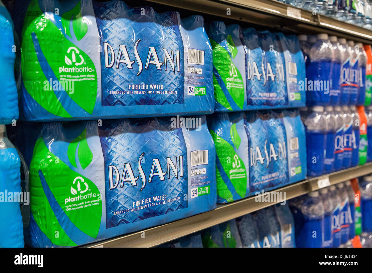 Packages of Dasani brand water bottles sit on the shelves of a grocery store - Stock Image