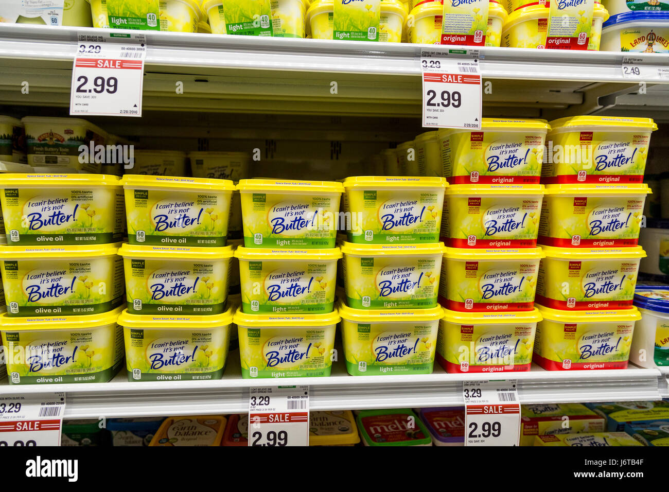 tubs of I Can't Believe its Not Butter brand non dairy spread in the refrigerator section of a grocery store - Stock Image