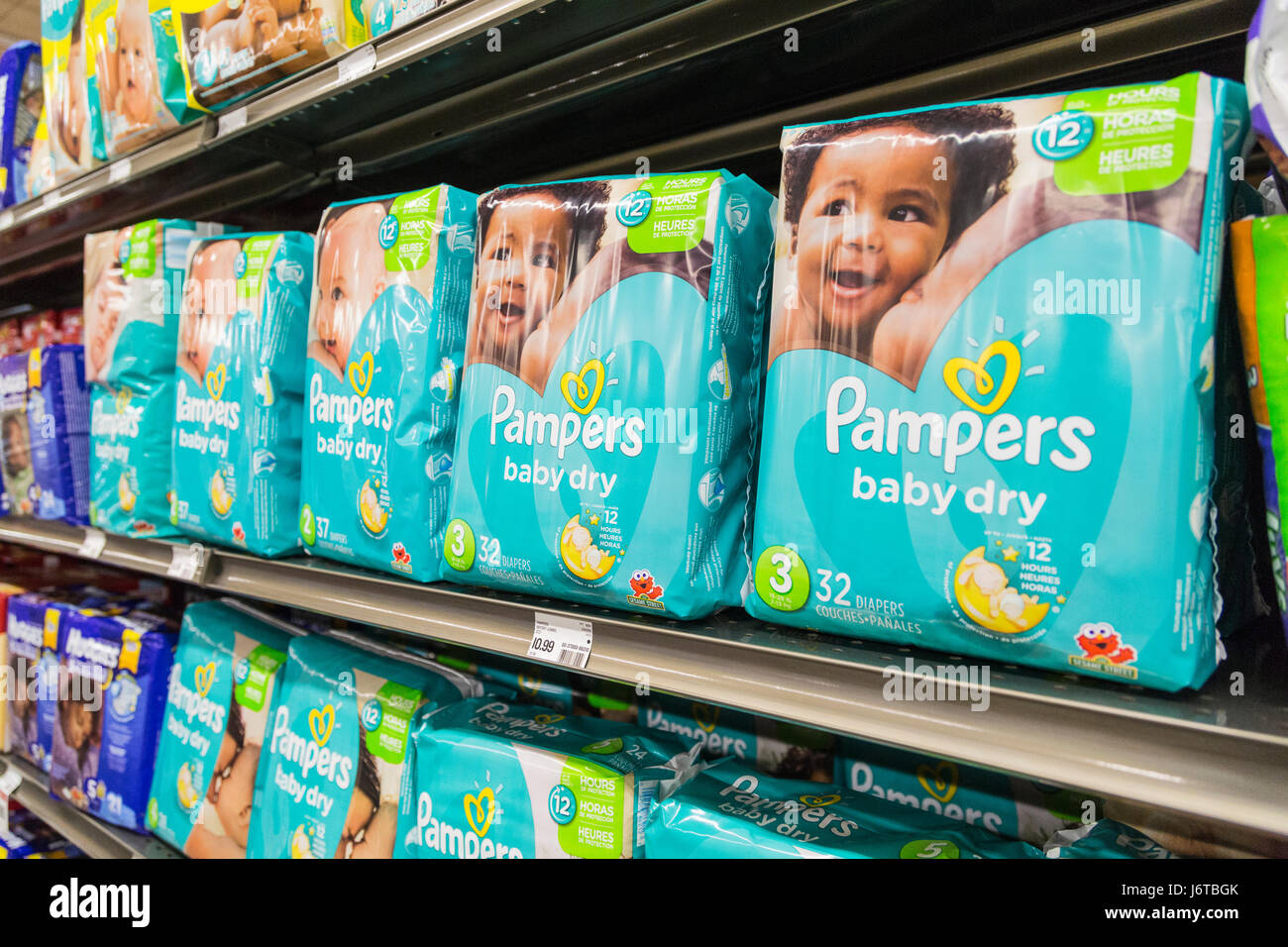 packages of Pampers brand diapers on a shelf of a grocery store - Stock Image