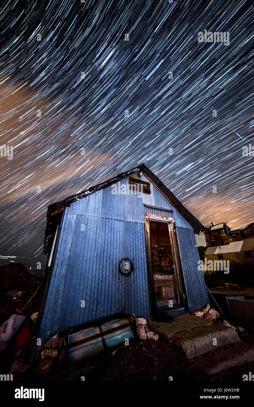 Star trail photography captures the path of distant stars framed against an old minimg shack as the earth rotates. - Stock Image