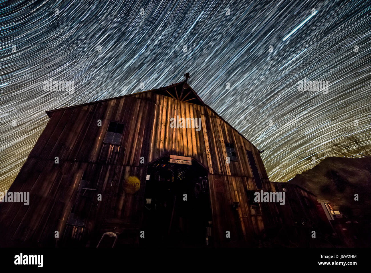 Star trail photography captures the path of distant stars over an old wodden barn as the earth rotates. - Stock Image