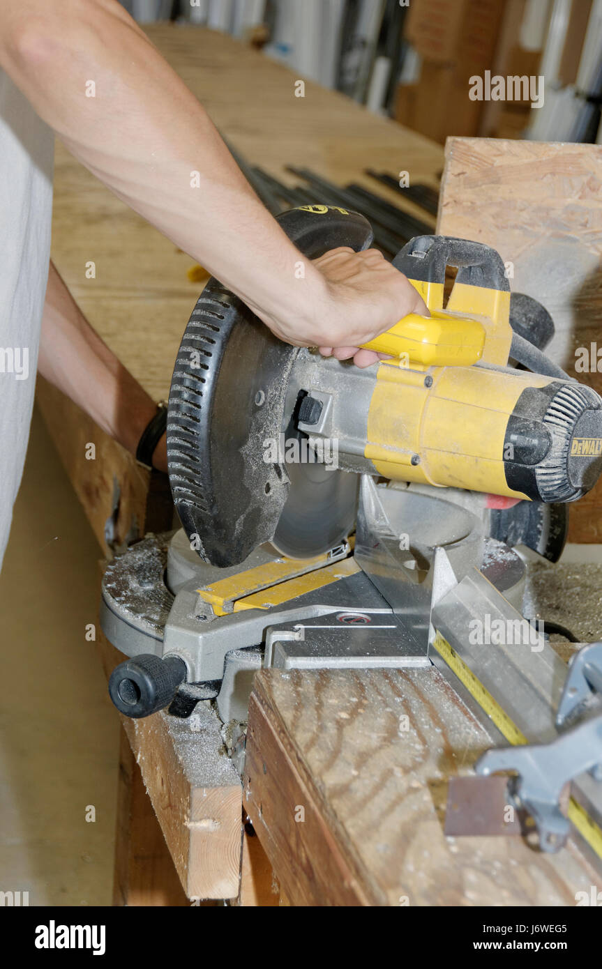 Male worker operatioing an industrial miter saw / chop saw. Stock Photo