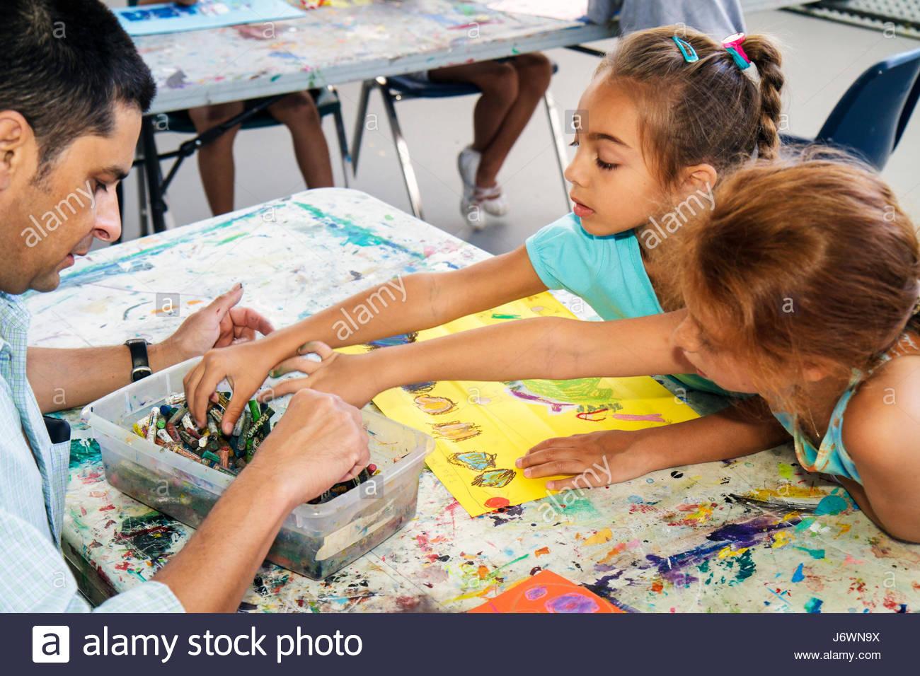 Miami Beach Florida ArtCenter South Florida Art Camp class Hispanic girl man teacher chalk drawing - Stock Image