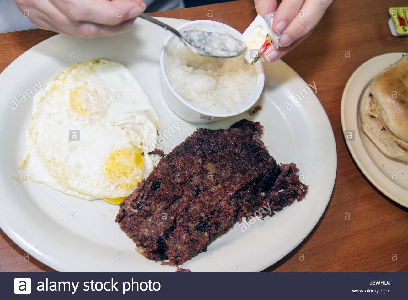 Miami Beach Florida 41st Street Roasters NY Deli restaurant food eggs grits adding butter - Stock Image