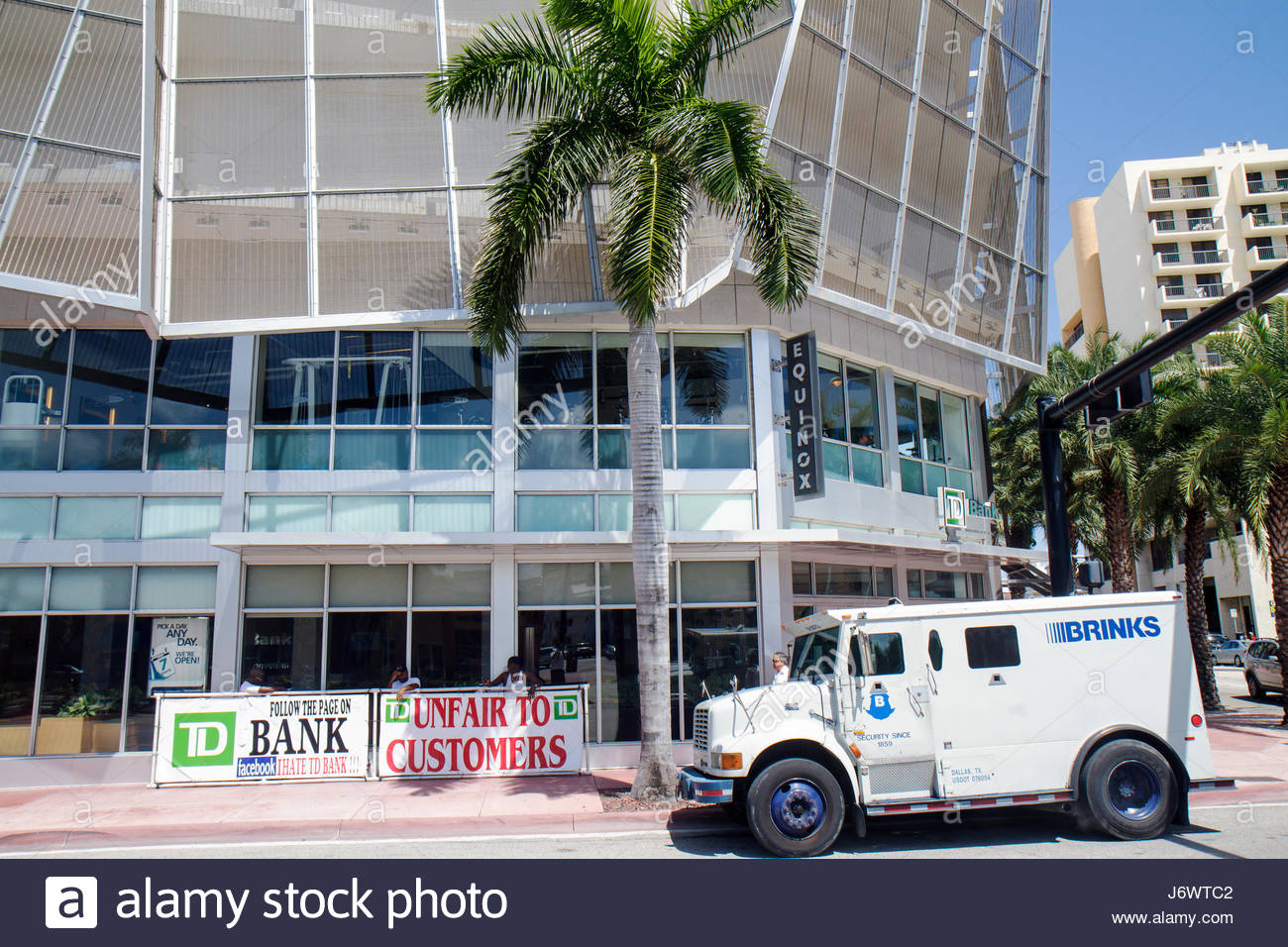 Miami Beach Florida TD Bank signs picketing Brinks armored truck - Stock Image