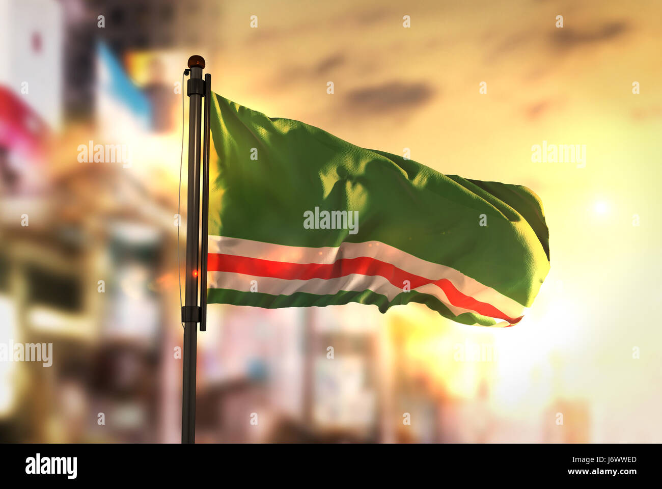 Chechen Republic of Ichkeria Flag Against City Blurred Background At Sunrise Backlight - Stock Image