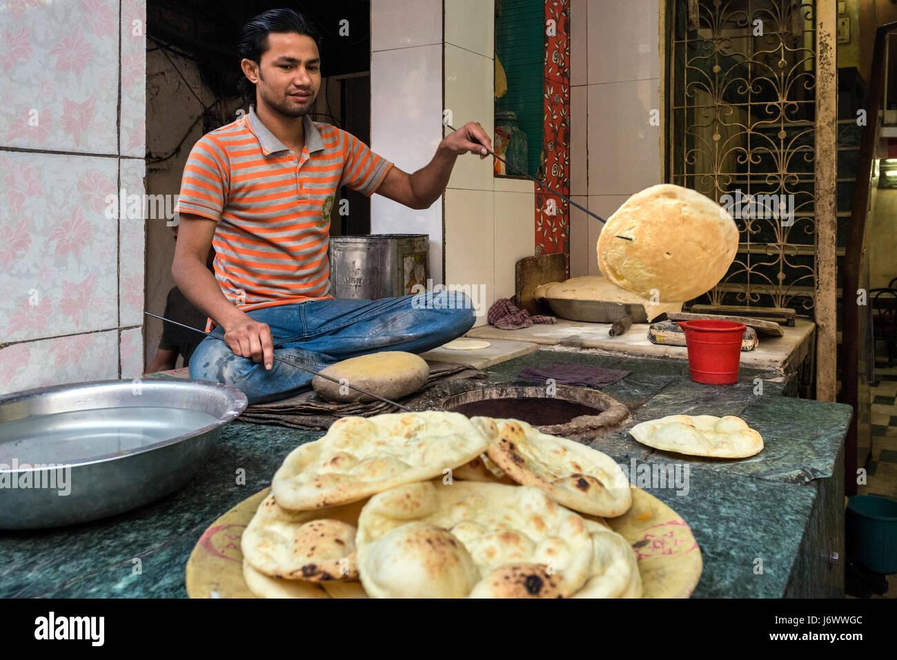 Delhi, India - 11 November 2012 - Man baking the naan in the oven in Delhi - Stock Image