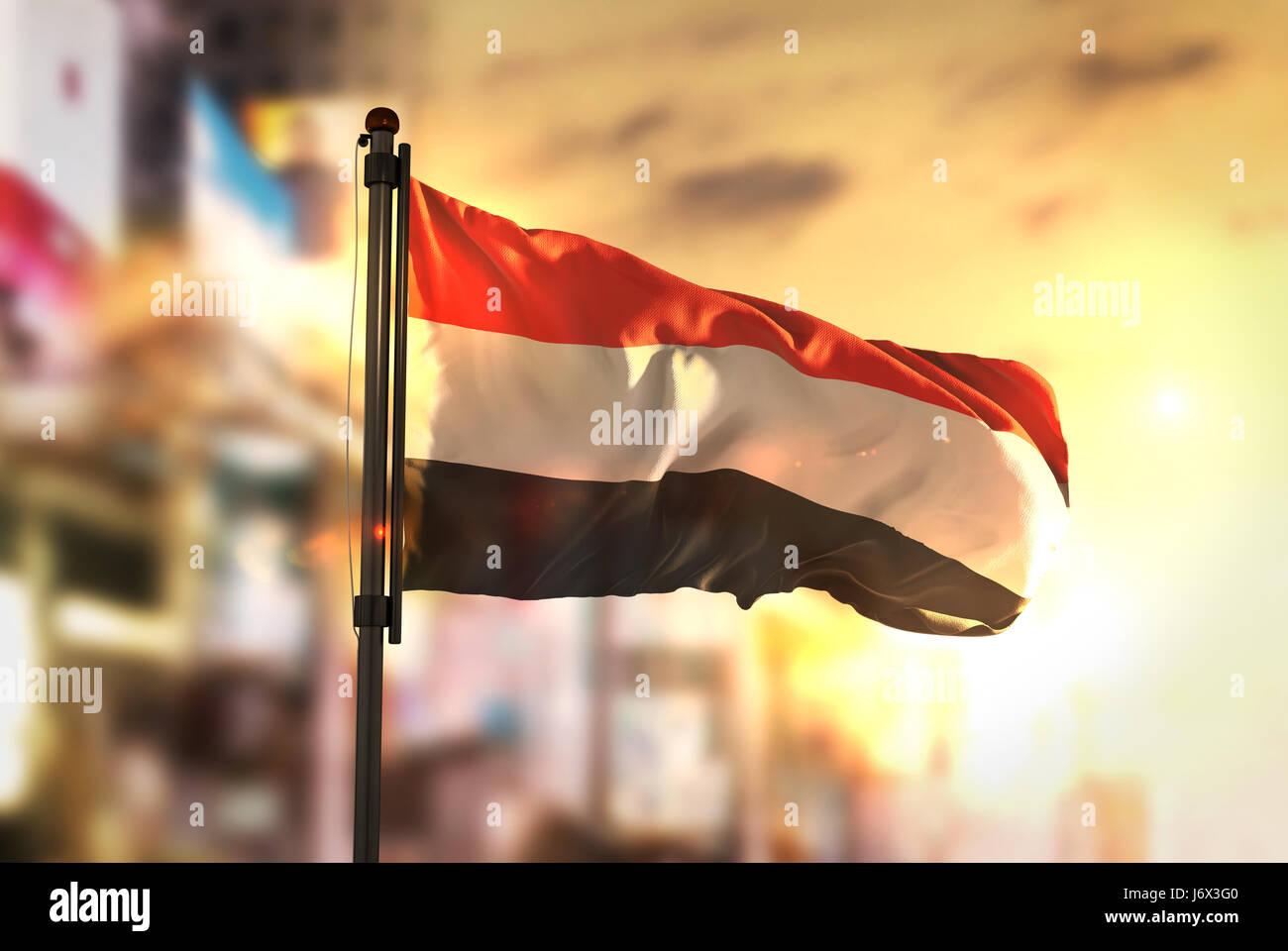 Yemen Flag Against City Blurred Background At Sunrise Backlight Stock Photo