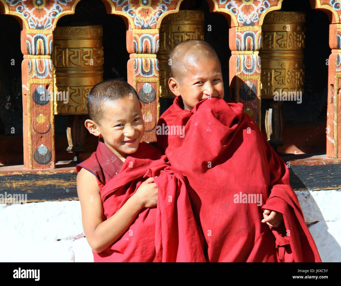 PARO, BHUTAN - NOVEMBER06,2012 : Unidentified smiling young monks standing by the religious prayer wheels at Paro - Stock Image