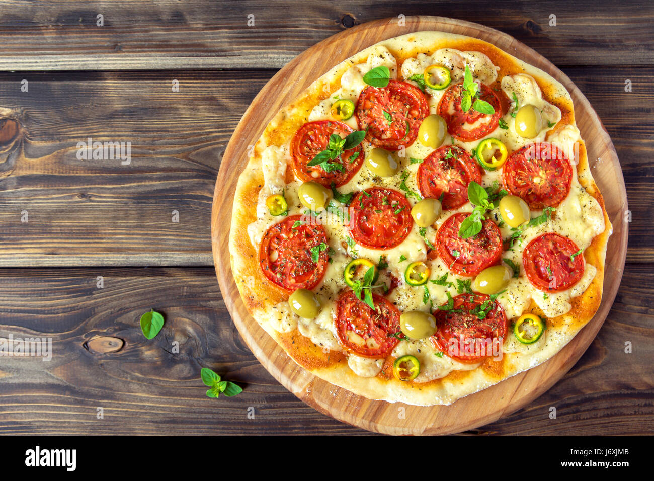 Italian Pizza with Tomatoes, Pepper, green Olives, Oregano and Mozzarella Cheese close up. Fresh Homemade Vegetable - Stock Image
