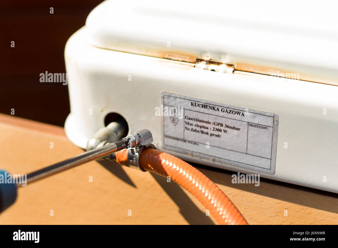 Install the flexible hose to the gas stove using a clamping band. - Stock Image