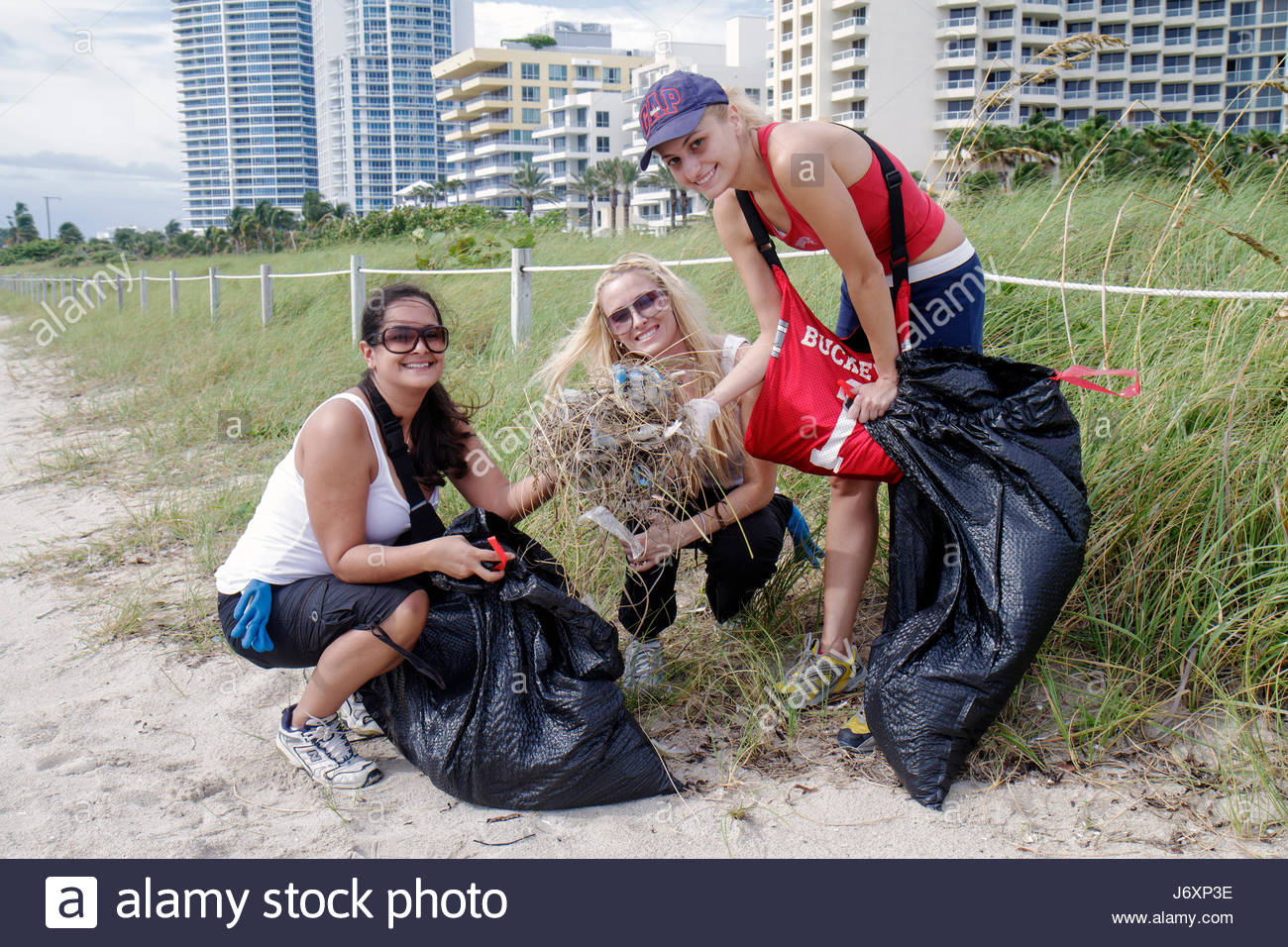 Miami Beach Florida Coastal Cleanup Day student volunteer litter trash pollution woman women public beach pick up - Stock Image